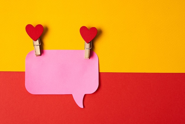 Pink notes on a yellow-red background and clothespins with hearts