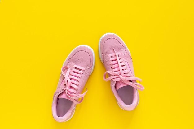 黄色の背景に分離されたピンクのヌバックスニーカー、ウォーキングやスポーツ用の季節の靴、上面図