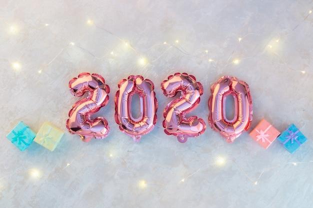 白いコンクリートにピンクの数字2020、カラフルなライトがきらめく星の花輪。
