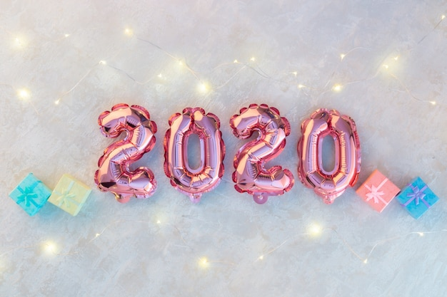 Pink numbers 2020 on white concrete, a garland of stars shimmering with colorful lights.