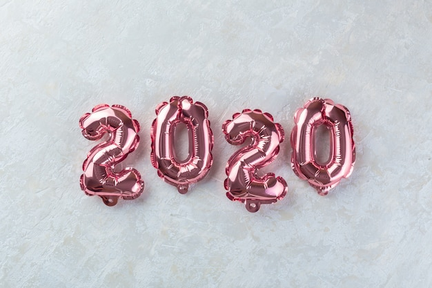 Pink numbers 2020 on white concrete