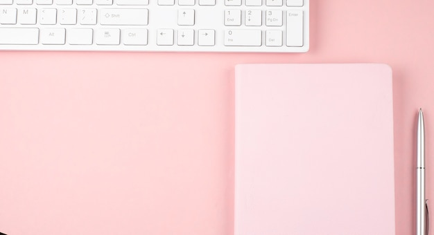 Pink office desk with keyboard and notebook.top view with copy space