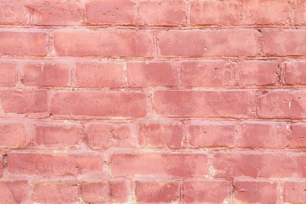 Розовая старая кирпичная стена с краской