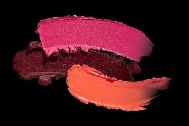 ピンクオレンジバーガンディのスミアの口紅の背景のテクスチャの汚れは黒で隔離