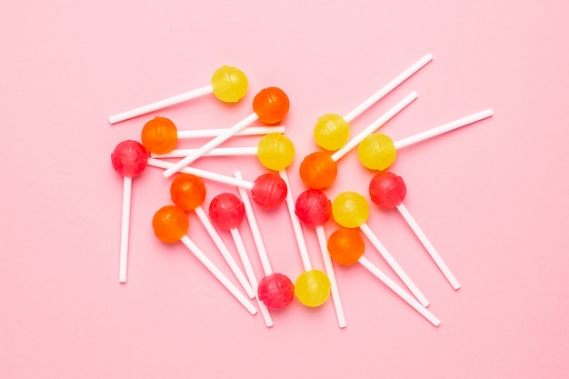 Pink, orange and yellow sweet candy lollipop on pastel pink