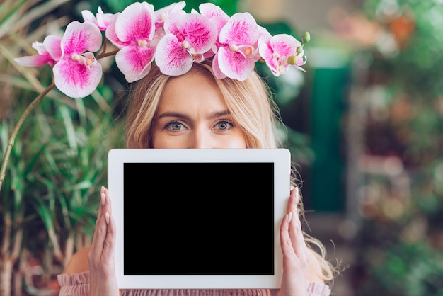 Pink orchid branch over her head holding blank digital tablet in front of her mouth