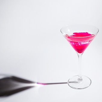 Pink paint dissolving in martini glass against white background