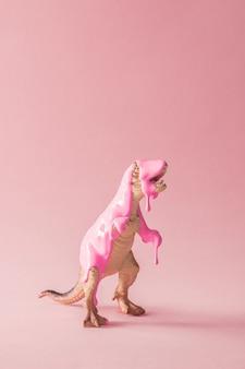 Розовая краска капает на игрушку динозавра
