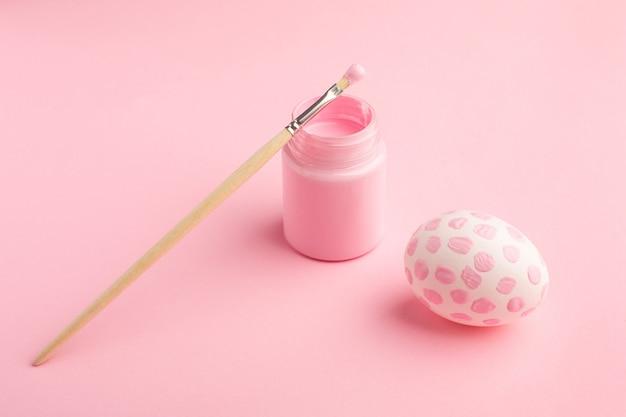 Розовое пасхальное яйцо и кисть. концепция праздника пасхи.