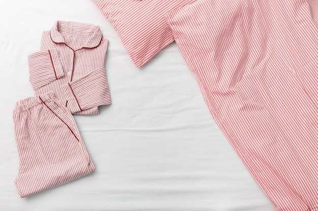 Pink pajamas folded bed, blanket and pillow in bedroom of house.