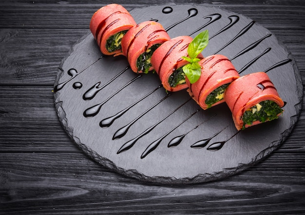 Pink pancakes stuffed with spinach and cream cheese on wooden background