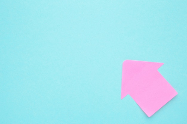 Pink paper arrow shapes on blue background for creative projects. top view