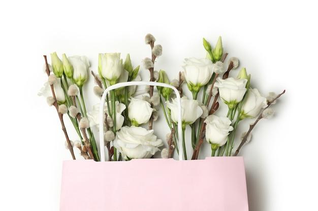 Розовый бумажный пакет с розами и сережками ивы, изолированные на белом фоне