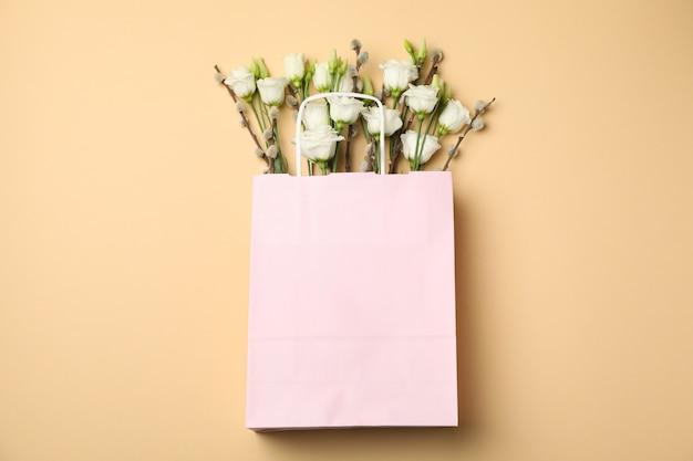 Розовый бумажный пакет с розами и ивовыми сережками на бежевом фоне