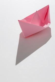 Розовый бумажный кораблик на белом фоне