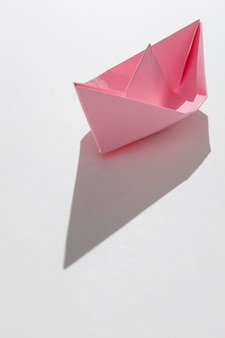 Pink paper boat on white background