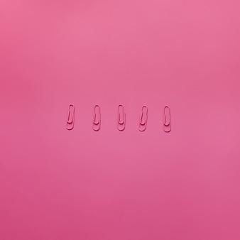 ピンクの背景にピンクのペーパークリップ。横型