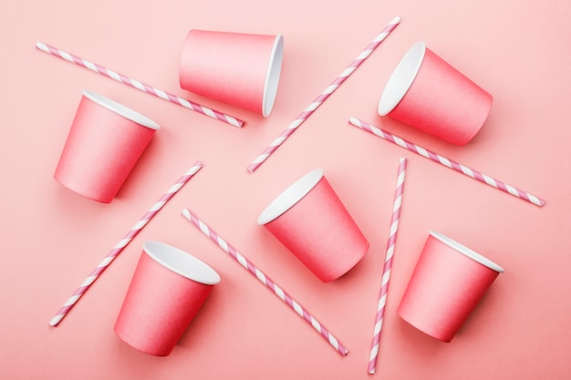 Pink paper cups and pink-white straw on pink