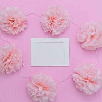 Pink paper cuted flowers and white frame with white blank