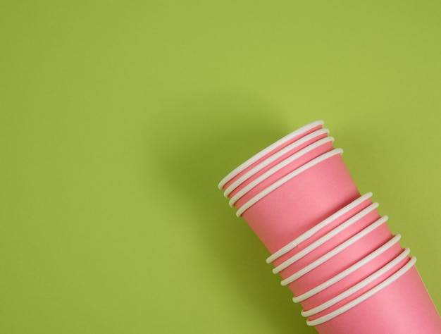 Pink paper disposable cups on a green surface, concept eco-friendly, zero waste