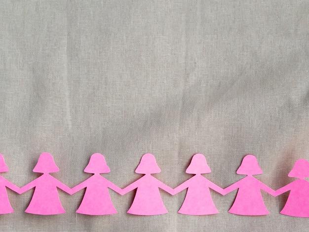 手を繋いでいるピンクの紙の女の子