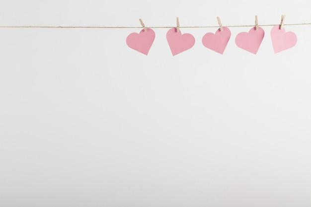 ロープにぶら下がっているピンクの紙の心
