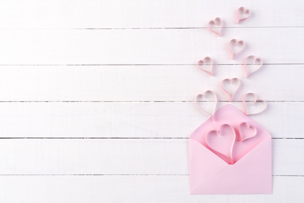 Pink paper hearts splash out from letter cover on white wooden background.