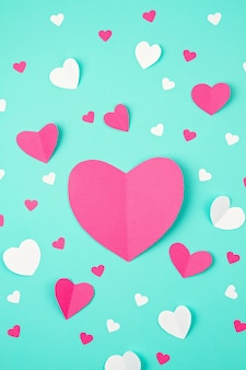Pink paper hearts over the turquoise background. sainte valentine, mother's day, birthday greeting cards, invitation, celebration concept