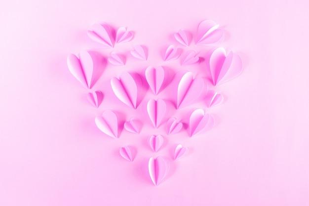 パステルピンクの背景にハートの形のピンクの紙。バレンタイン・デー