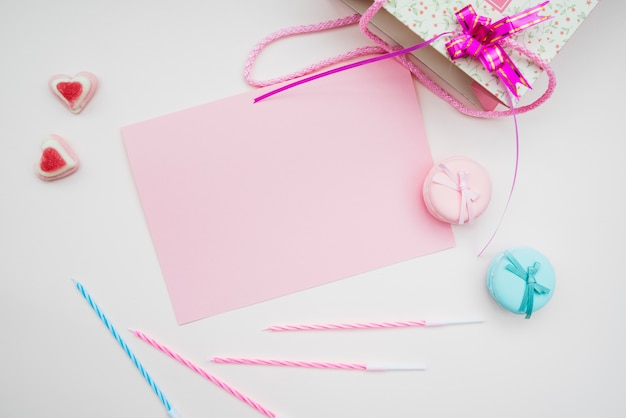 Pink paper; macarons; candles and heart shape candies and shopping bag on white background