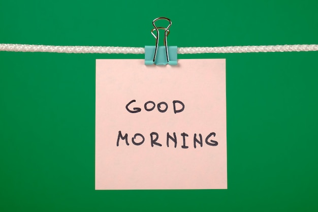 Pink paper note on clothesline with text good morning