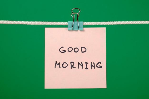 Розовая бумажная записка на бельевой веревке с текстом «доброе утро»