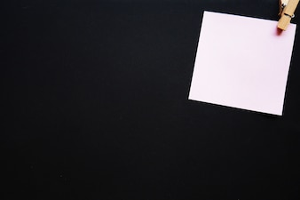 Pink paper note with wooden peg on black board