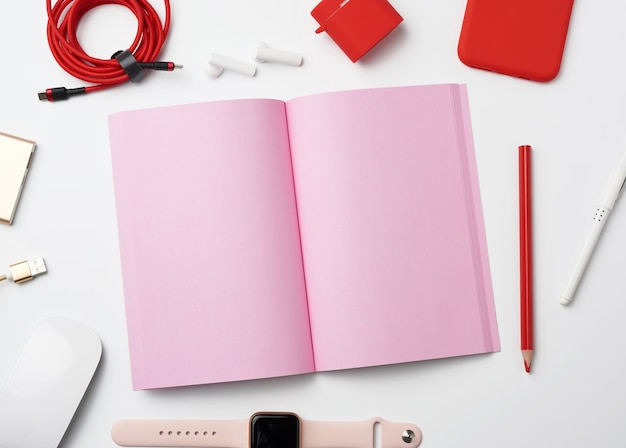 Pink paper notebook, power bank with cable, red smartphone, headphones, wireless mouse and smart watch