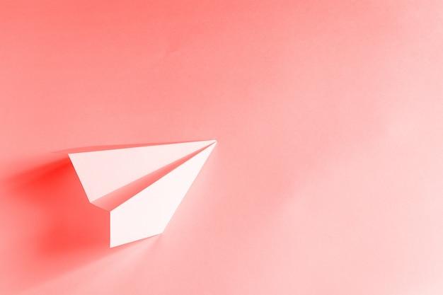 サンゴの背景にピンクの紙飛行機