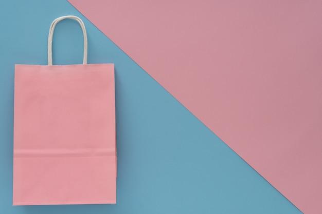 ピンクと青の背景にピンクの紙の買い物袋。上面図..テキストの場所、