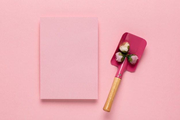 Pink paper and shovel with flowers