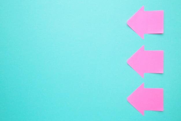 파란색 배경에 화살표의 모양에 분홍색 종이 스티커 메모