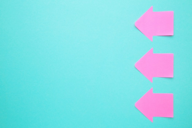 Pink paper sticky notes in shape of arrow on blue background