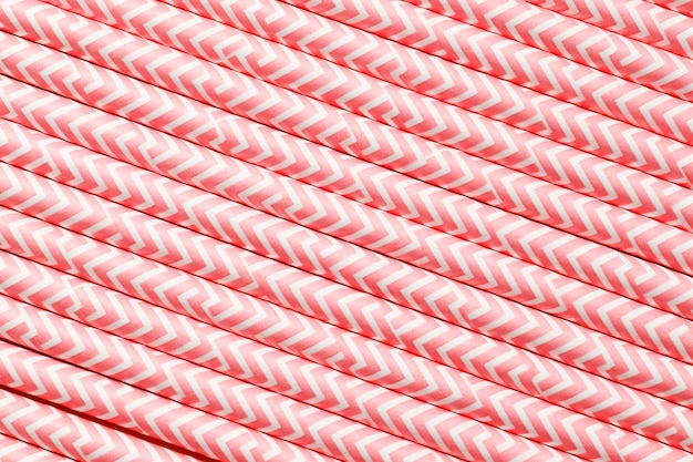 ピンクの紙ストロー。背景のクローズアップとしてのカクテルチューブ