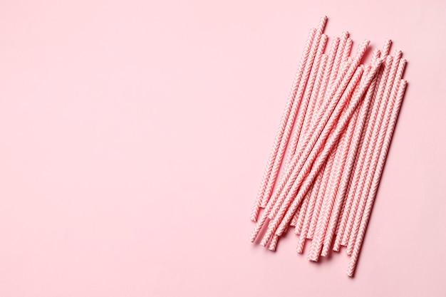 텍스트를 위한 장소가 있는 분홍색 배경에 분홍색 종이 빨대.