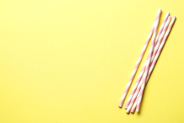 黄色の背景にピンクの紙ストロー