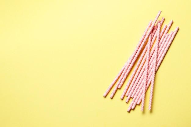 분홍색 종이 빨대 . 텍스트를 넣을 수 있는 노란색 배경에 칵테일을 위한 분홍색 세관