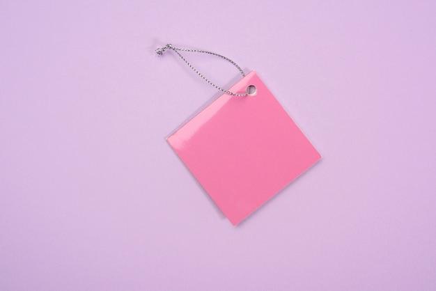 Розовая бумажная бирка на фиолетовом фоне, плоская планировка