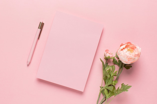 Pink paper with pen and flowers
