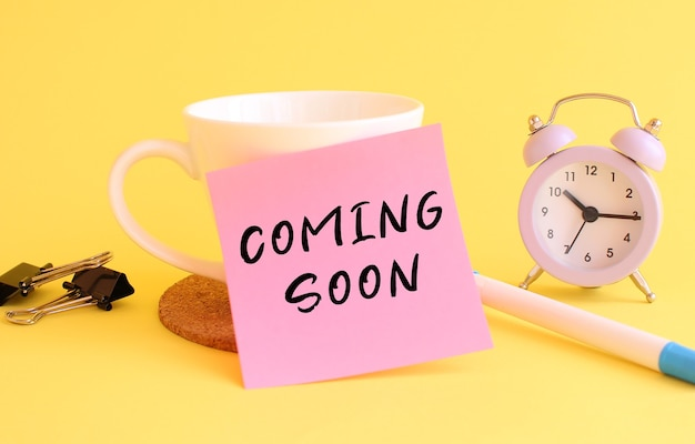 Pink paper with the text coming soon on a white cup. clock, pen on a yellow table.