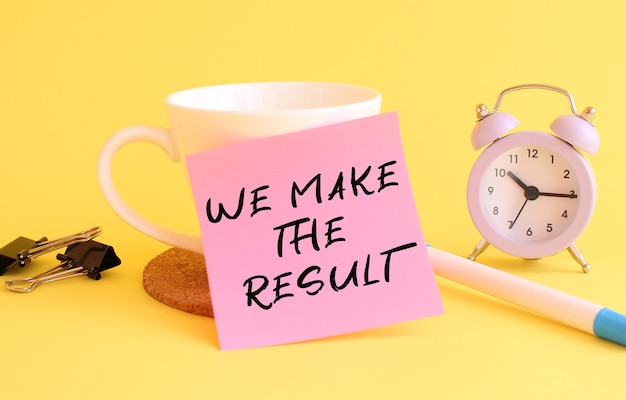 Pink paper with the text we make the result on a white cup. clock, pen on a yellow background. design concept.