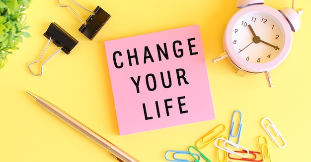 Розовая бумага с текстом измени свою жизнь. часы, ручка на желтом фоне. концепт дизайна.