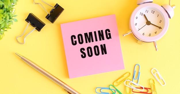 Розовая бумага с текстом скоро в продаже. часы, ручка на желтом фоне. концепция дизайна.