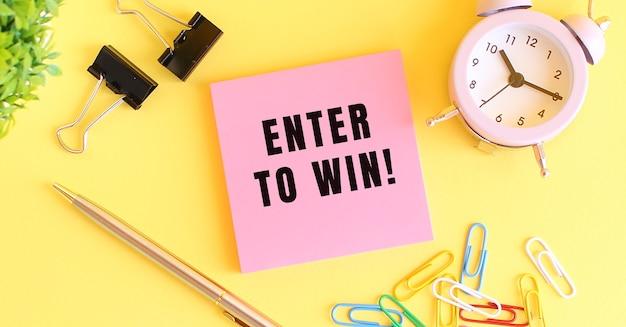 Розовая бумага с надписью enter to win. часы, ручка на желтой поверхности